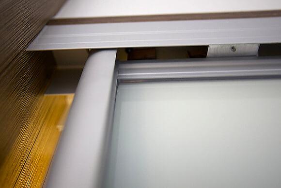 Horní vodící lišta posuvných dveří, kde je ukryta baterie napájející LED osvětlení.