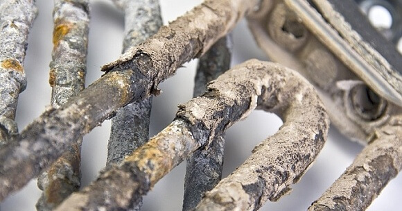 Vodní kámen usazený na topném tělese pračky (zdroj: www.altamore.cz)