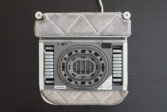 Spodní část umývače oken Ecovacs Winbot W710. Nahoře přední textilie, která se navlhčí čisticím prostředkem, pod ní stěrka, sací komory a silikonové pásy pro pohyb a dole utěrka na dočištění.