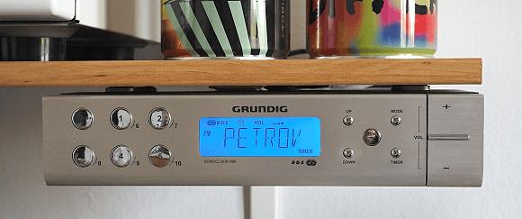 Kuchyňské rádio namontované na polici ze spodní strany.